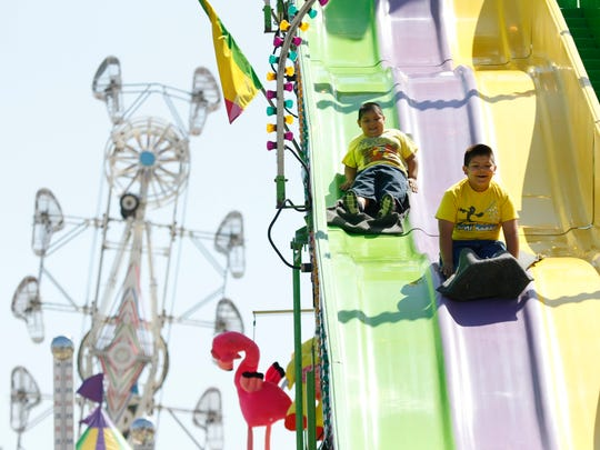 Santiago Flores (right), 6, and his brother Emilio Flores, 5, enjoy a ride down the slides.