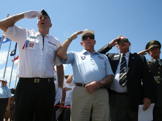 Dick Sayers, second from left, salutes during the U.S. national anthem Sunday at Ecological Park at the Korean War Veterans Memorial Dedication in 2008.