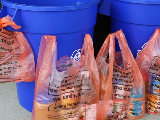 Look for the orange Curbing Hunger bags tied to your