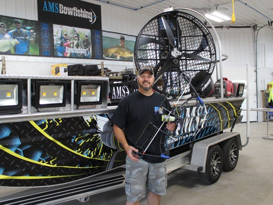 Matt Schillinger poses with his fishing bow in front