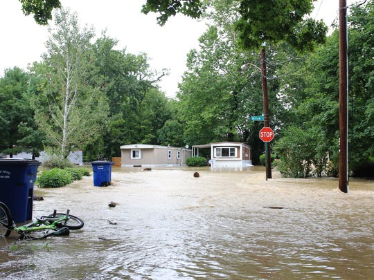 Floodwaters flow through downtown Pataskala, carrying logs, tires and other debris.