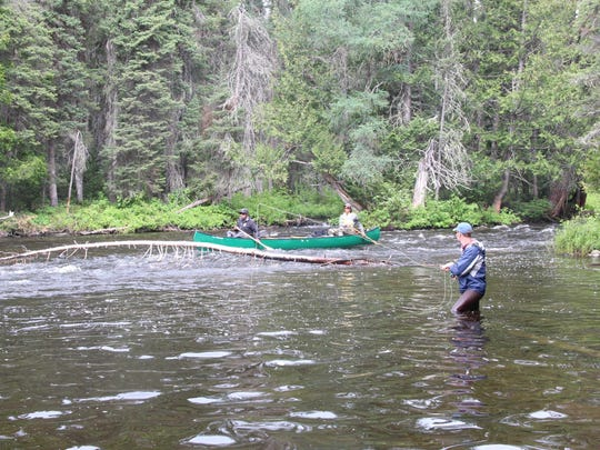 Matt Reilly fishes for brook trout as guides Keith Missewace and Joe Boyce canoe down a stretch of river in northwestern Ontario.