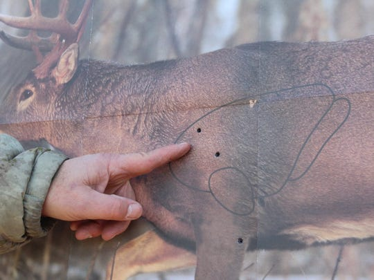 Tony Gailloreto examines bullet holes on a deer target during a sight-in clinic at Milford Hills Hunt Club in Johnson Creek, Wis.