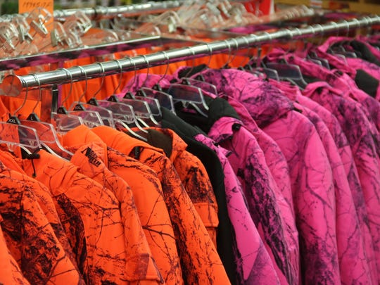 Blaze pink and blaze orange hunting coats hang from a rack. Blaze pink was legalized in 2016 as a legal color for deer hunting in Wisconsin, but demand has been soft for the pink products, according to several retailers.