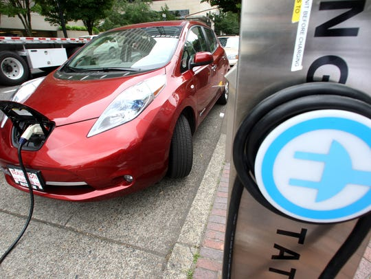 A Nissan Leaf charges at an electric vehicle charging
