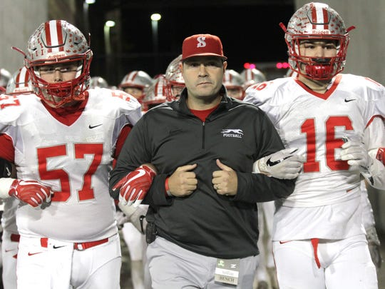 Shelby head coach Erik Will locks arms with his players before playing against Steubenville in the state semifinals at Akron University on Friday night.