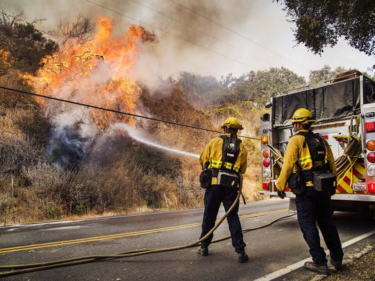 Firefighters battle flames on Highway 150 between Carpinteria and Ojai on Monday.  The Thomas Fire continues to burn and is now the fifth largest in California history.
