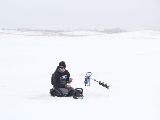 Tyler Mohr of Winona, Minn. ice fishes on Devils Lake, North Dakota.