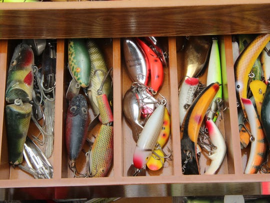 Vintage fishing lures line a tackle box.