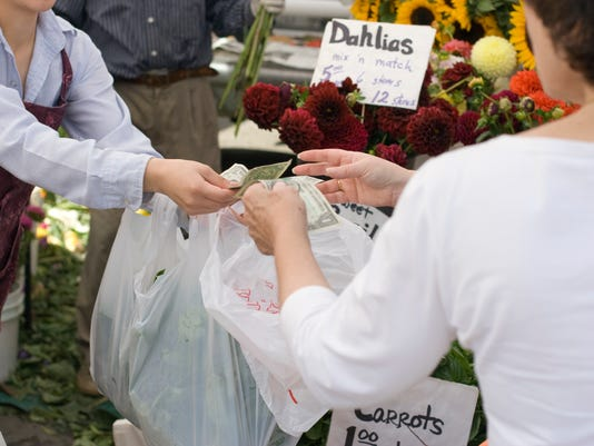 Paying cash for fresh produce at farmers market