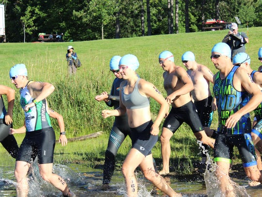 Triathletes enter the water in a past Woodson YMCA