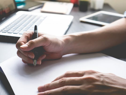 male hands writing on paper on his desk.