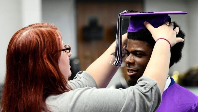 FILE: Kirsten Buckner helps I'Shjumere Westbrook with his mortar board as students at Evansville's Academy for Innovative Studies First Avenue prepare to enter the auditorium for their graduation ceremony.