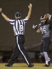 Brett Teller shows the ball to the referee after a