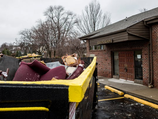 Furniture and other items are seen in a dumpster from interior water damage at The St. Clair Inn.