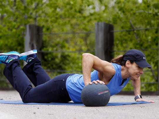 Catherine Andersen shows the ending position for the medicine ball pushup exercise.