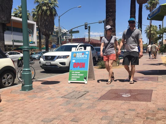 A couple strolls along Palm Canyon Drive in downtown Palm Springs.