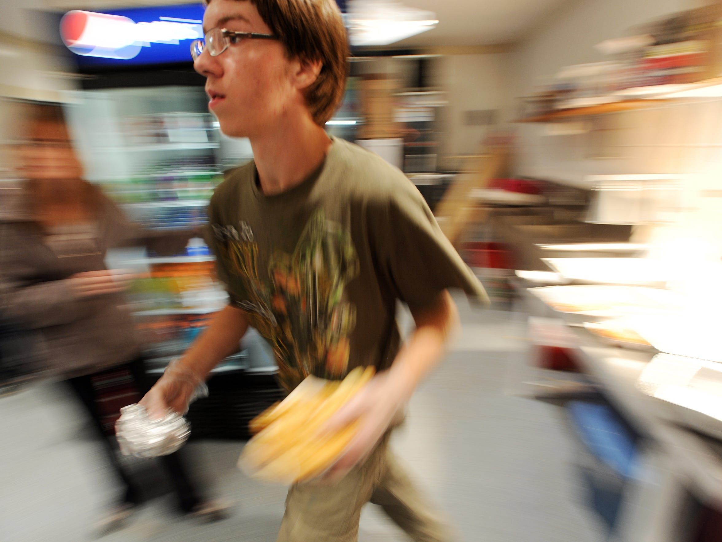 Steven Colona rushes an order to the Nandua concession stand window during a halftime rush on Friday, Oct. 3, 2014.