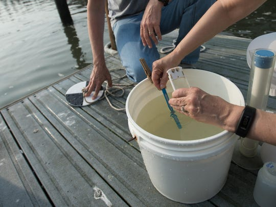 Bev Stoner takes the temperature of a water sample.