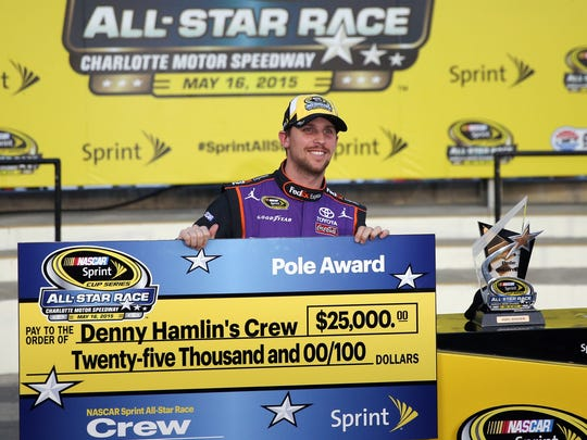 Denny Hamlin celebrates after winning the pole for