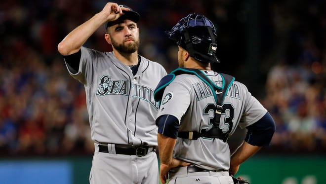 Seattle Mariners starting pitcher Nathan Karns, left, talks with catcher Chris Iannetta in the third inning of a baseball game against the Texas Rangers on Saturday, June 4, 2016, in Arlington, Texas. (AP Photo/Tony Gutierrez)
