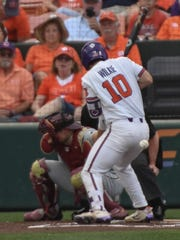 Clemson sophomore catcher Kyle Wilkie (10) is hit by