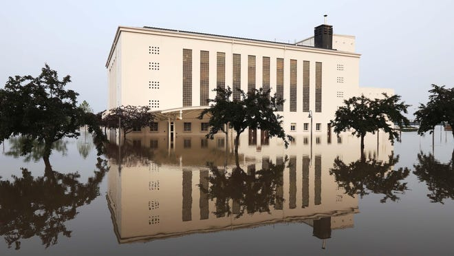 Memorial Auditorium is reflected in the floodwater from the Mississippi River after a break in the flood barriers floods downtown June 1, 2019, in Burlington. The first 2021 flood prediction report puts the chance of flooding at 60%.