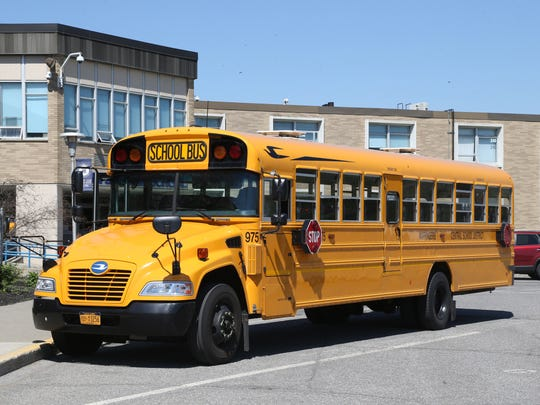 In this file photo on May 9, 2018, a school bus waits outside John Jay High School.