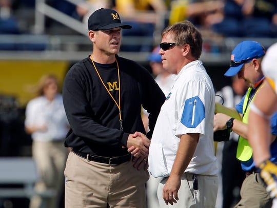 Michigan coach Jim Harbaugh, left, and then-Florida coach Jim McElwain meet at midfield before the 2016 Citrus Bowl on Jan. 1, 2016.