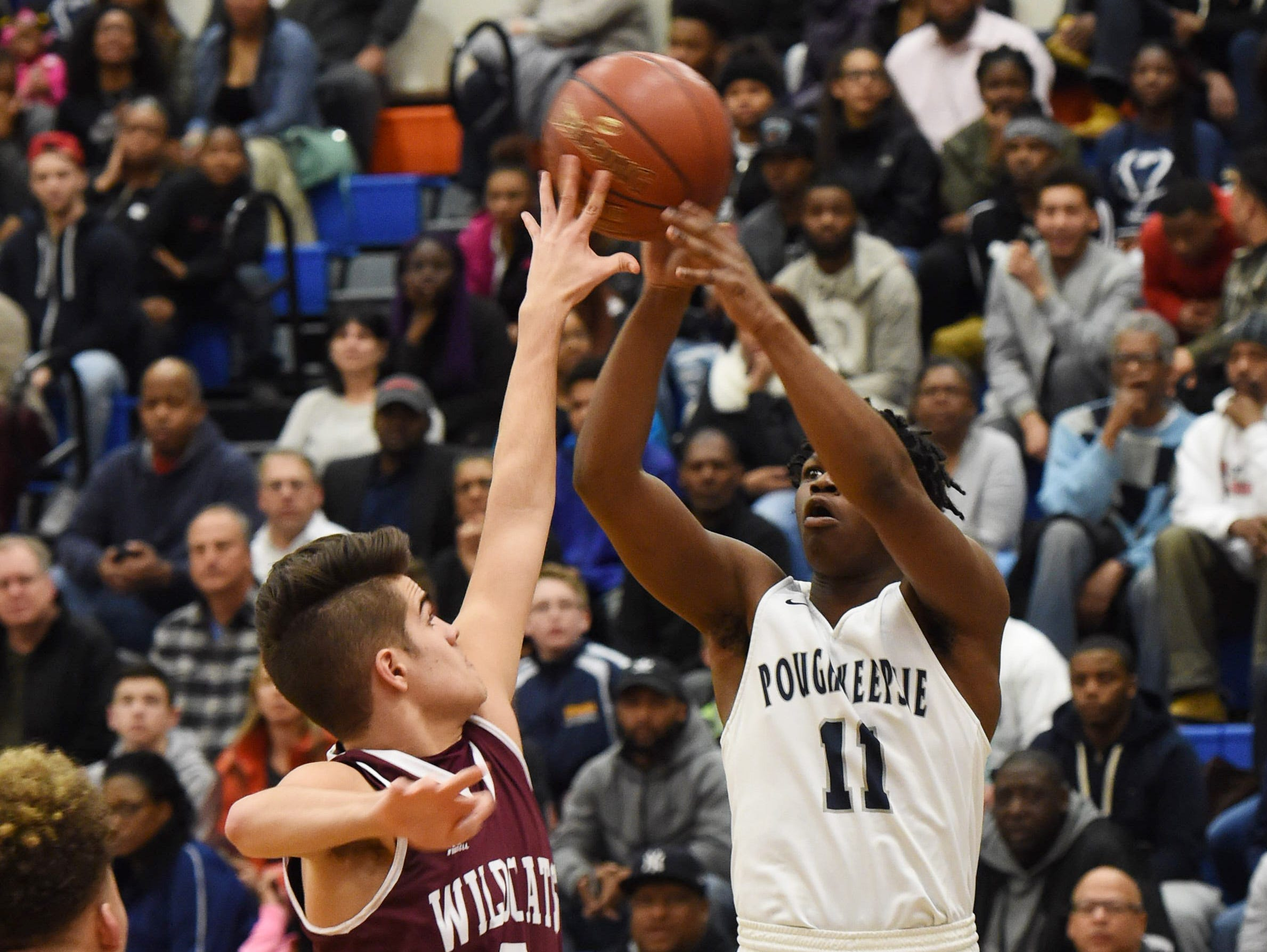 Poughkeepsie High School's Anatwone West, right, takes a shot while Johnson City's Alec Lopez, left, defends during the Class A regional semifinal game at SUNY New Paltz.