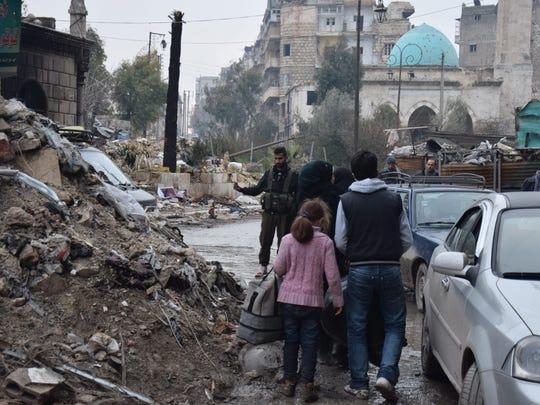 Inhabitants of the al-Kallasseh area walk in the eastern