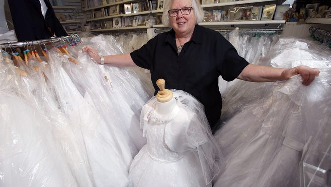 Irish gift shop Faith and Begorra owner Susan Banks with some of her hundreds of communion dresses in their Denville showroom. March 8, 2016. Denville, N.J.