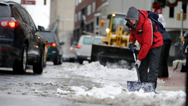 Workers clear snow from a street on Tuesday in Trenton, N.J.