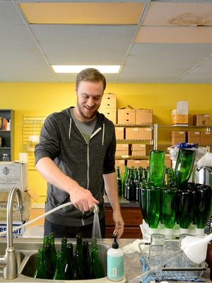 Jacob Schopp, general manager of Capital City Homebrew Supply, cleans bottles at the shop at 2016 E. Michigan Ave. The store is going to move after being in its current location for a year because developer Scott Gillespie plans to tear down the building for a new development. The shop will relocate to the 600 block of Michigan Avenue by the beginning of January.