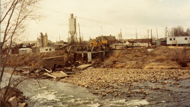 This faded color photograph shows the rubble of the Linden Street Bridge next to the Cache La Poudre River. An unidentified factory is visible on the opposite side of the river.