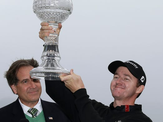 Jimmy Walker lifts his trophy on the 18th green of the Pebble Beach Golf Links after winning the AT&T Pebble Beach Pro-Am golf tournament Sunday, Feb. 9, 2014, in Pebble Beach, Calif. Walker shot a 2-over-par 74 to finish at total 11-under-par