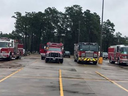 Fire trucks and other emergency vehicles wait to assist