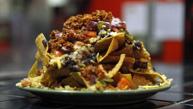 The Mexican Plate at John's Tex-Mex includes a choice of proteins plus John's Mexican Mush, rice, tomatoes and more piled on top of tortilla chips.