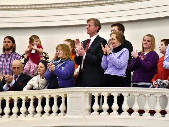 Republican gubernatorial candidate Scott Milne (center) applauds as his father, Donald Milne, is escorted into the House chamber after being re-elected clerk of the House on the opening day of the Legislature at the Statehouse in Montpelier on Wednesday.