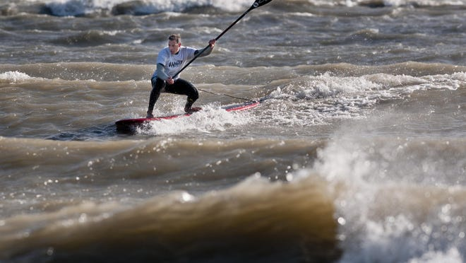 Brian LeFeve, of St. Clair Shores, surfs on his paddle board Wednesday on Lake Huron in Lexington.