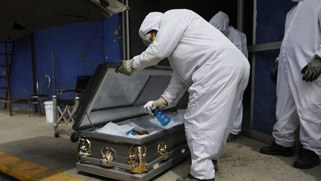 A worker wearing protective gear sprays disinfectant solution inside the coffin of a person who died from suspected COVID-19, as the body arrives at the crematorium July 27 at Xilotepec Cemetery in Xochimilco, Mexico City.