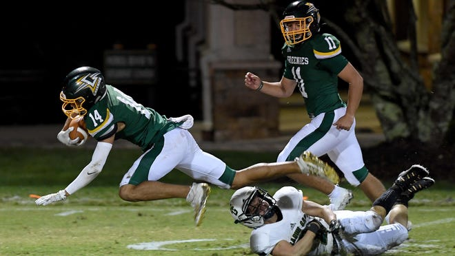 Christ School's Painter Richards-Baker gets tripped up by  Rabun Gap-Nacoochee's Joseph Caiata as he runs the ball during the Greenies' season-opening game on Sept. 25.