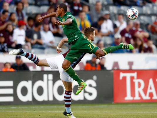 Portland Timbers defender Roy Miller, front, collides with Colorado Rapids forward Kevin Doyle as they pursue the ball in the first half of an MLS soccer match Saturday, June 17, 2017, in Commerce City, Colo. (AP Photo/David Zalubowski)