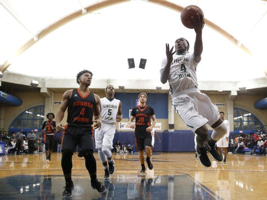 Lincoln sophomore Trinton Bryant lays the ball up past Orange Park's Darrell Vann during their Capital City Classic game at the TCC Eagledome on Monday.