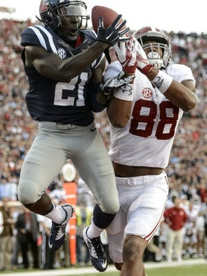 Ole Miss defensive back Senquez Golson (21) intercepts a pass in the end zone intended for Alabama tight end O.J. Howard (88) during the fourth quarter of an NCAA college football game in Oxford, Miss., Saturday, Oct. 4, 2014. No. 11 Mississippi beat No. 3 Alabama 23-17. (AP Photo/AL.com, Vasha Hunt)