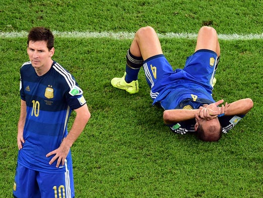 Argentina's Pablo Zabaleta lies on the pitch as Lionel Messi stands beside him after losing to Germany in the final.