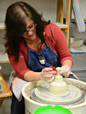 Juliet Faber builds handles for coffee mugs on her pottery wheel in her East China Township studio