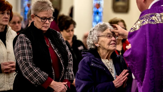 Marie Inscho receives ashes from Father Wilson during a lunchtime Ash Wednesday mass at Blessed Sacrament. Inscho, went to school at Blessed Sacrament in the 1930's.