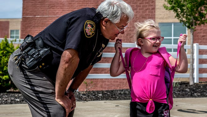 Coshocton City Schools' resource officer, Jeff Corder, greets Macie Dickerson, 7, after school as she heads home with her family.