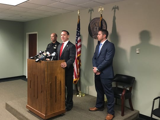 Prosecutor Rob Sanders, center, announces murder charges